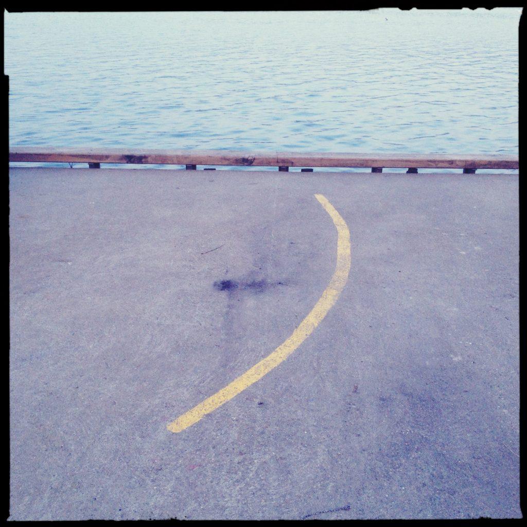 Markierungslinie, die auf einen See zuführt. Quadratisches Hipstamatic-Bild.