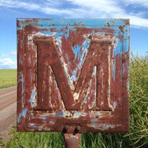 Rostiges ehemals blaues Metallschild, das ein M zeigt.