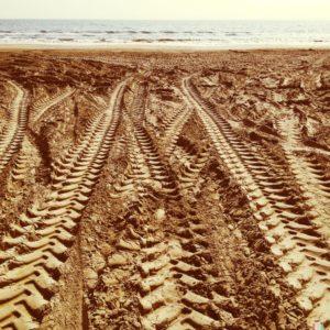 Traktorspur am Sandstrand, die auf das Meer zuführt.