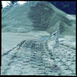 Reifenspur, die auf einen Kieshaufen zuführt, Froschperspektive