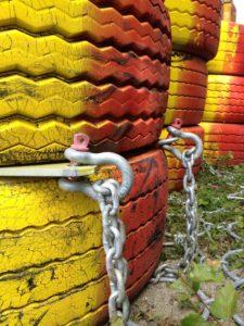 Rot-gelb bemalte alte Reifen, die von Ketten zusammengehalten werden - in Schweden dienen sie als Straßenblockade bei Baustellen