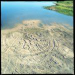 Reifenspuren im Sand eines Flussbettes. Man sieht türkisfarbenes Wasser und runde Reifenspuren