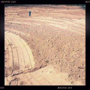 Frisch planierte Baustelle, im Hintergrund ragt ein Rohr aus der Erde.