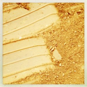 Glatte Reifenspur in gelbem Lehm, die plötzlich endet.