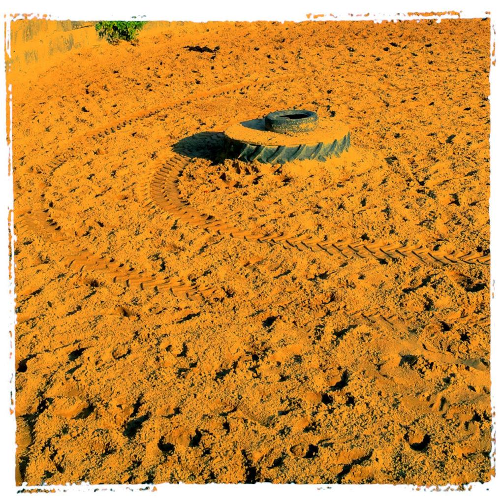 eine Traktorspur führt in geschwungener Kurve um einen alten Reifen, der als Hindernis in einer Pferdekoppel liegt. Ockergelbe Farbe übers ganze Bild.