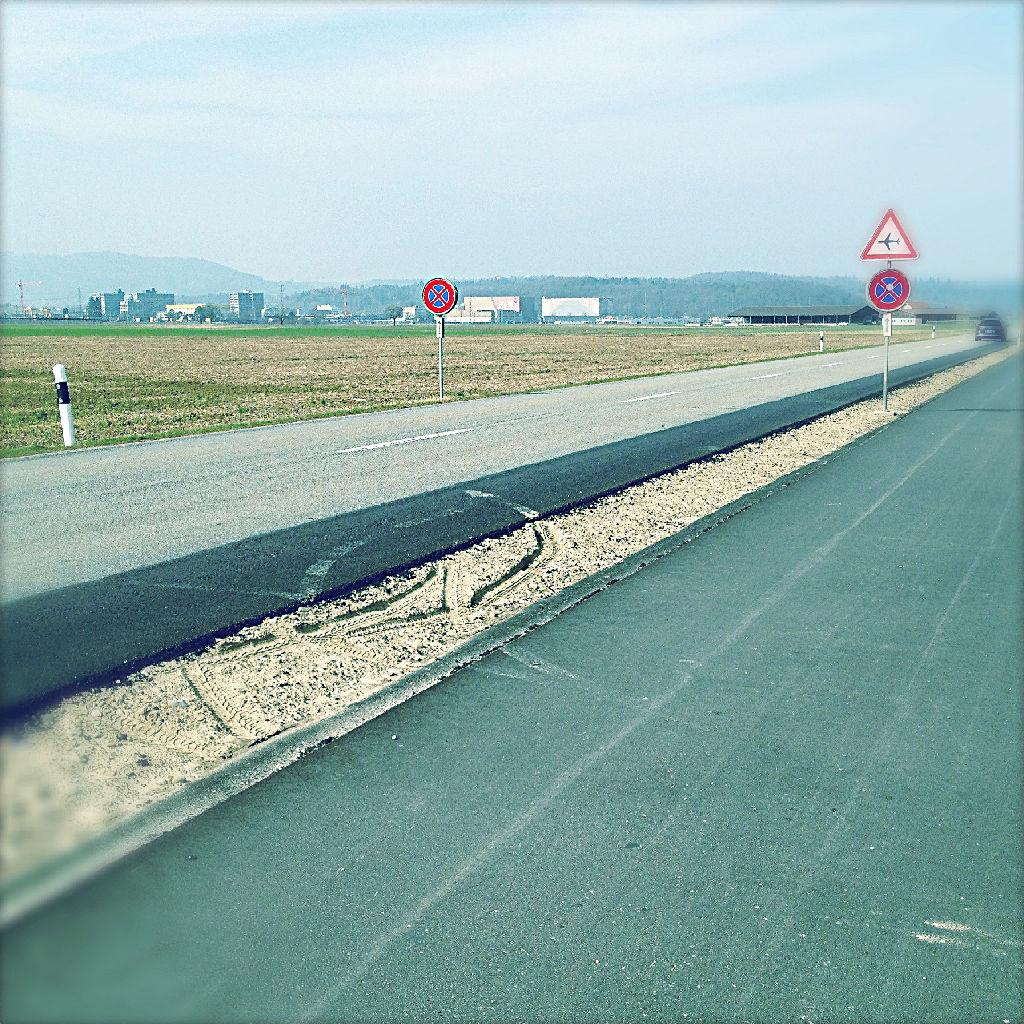 Zwischen einem geteerten Radweg und der Straße befindet sich ein schmaler, erdiger, unbewachsener Streifen, durch den sich eine Reifenspur zieht. Am Horizont des blassblaugrauen Bildes sieht man ein Warnschild, Halteverbotsschilder und Gebäude.