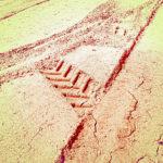ein rötlich-gelbliches Foto Blick auf eine Traktorspur, die zwei Reifenspuren so kreuzt, dass sich ein A im Sand abbildet.