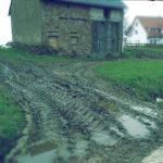 Im unteren Drittel des Bildes führt eine zerfahrene, matschige Fläche auf ein wenige Grün zu, aus dem sich eine alte, aus Sandsteinen gemauerte Scheune erhebt.