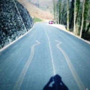 Blick entlang einer Teerstraße auf eine beigefarbene Spur, die in der Bildmitte endet. Im Vordergrund sieht man den Schatten des Fotografen, im Hintergrund, rechts am Straßenrand winzig ein PKW.