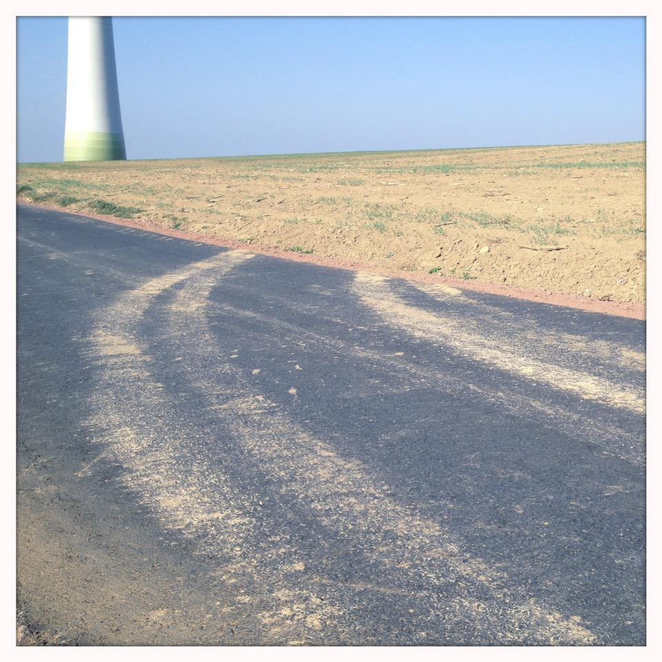 Auf einem Teerweg vor dem andeutungsweise sichtbaren Fuß einer Windanlage führt eine hellbraune LKW-Spur abseits in ein abgeerntetes Feld. Der Bildhorizont liegt im oberen Fünftel des quadratischen Bilds. Blasse Pastellfarben in blau-gelb-beige