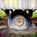 Mittig im Bild der platte Reifen eines Bauwagenrads unter rostiger, eiserner Achskonstruktion und Verbretterung des Aufbaus mit abblätternder, gelber Farbe.