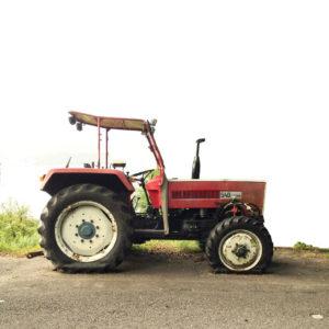 Roter Traktor vor freigestelltem weißem Hintergrund auf Teerstraße und einem Streifen Grase. Die Maschine im Profil, von links nach rechts zu fahren scheinen hat zwei platte Reifen. Die anderen beiden Reifen sieht man nicht.