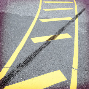 Gelbe Sperrmarkierung auf Asphalt, durch die von links unten nach rechts oben ein schwarzer Gummistreifen von Brems- oder Beschleunigungsabrieb eines Autoreifens führt.