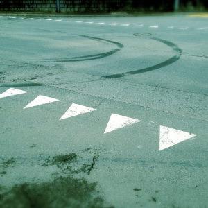 Eine grünlich-bläulich verfärbte Teerfläche. Die Straßenmarkierungen einer Einmündung zeigt kleine weiße Dreiecke, die wie spitze Zähne in Richtung des Betrachters zeigen. Darüber eine nach links kurvende Spur von Gummiabrieb.