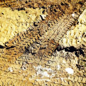 Schräge Spur eines LKW-Reifen auf lehmig gelblich-bräunlicher Oberfläche, von oben betrachtet und Bildfüllend nur Schlamm und Spuren.