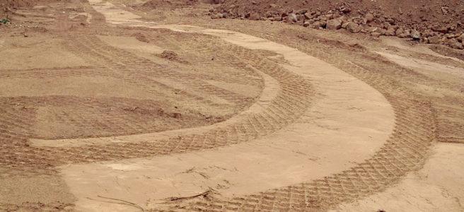 Planiertes Gelände vor einem halb abgerissenen Betongebäude. Die rautenförmige Spur breiter Reifen zeichnen sich im sandigen Untergrund ab und bilden eine 90 Grad Linkskurve.